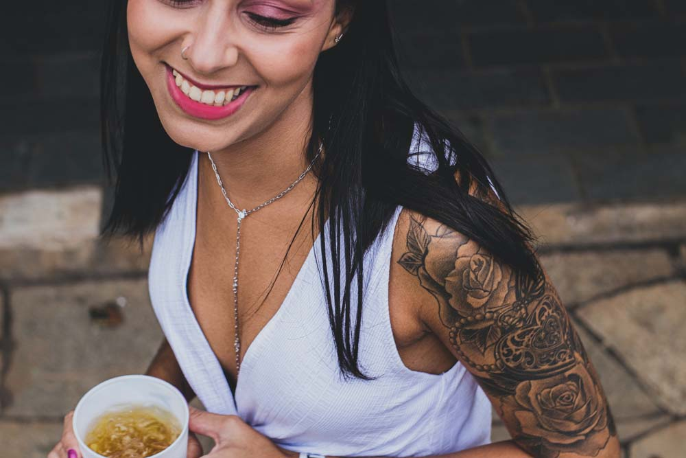 Woman with upper arm tattoo holding noodles.