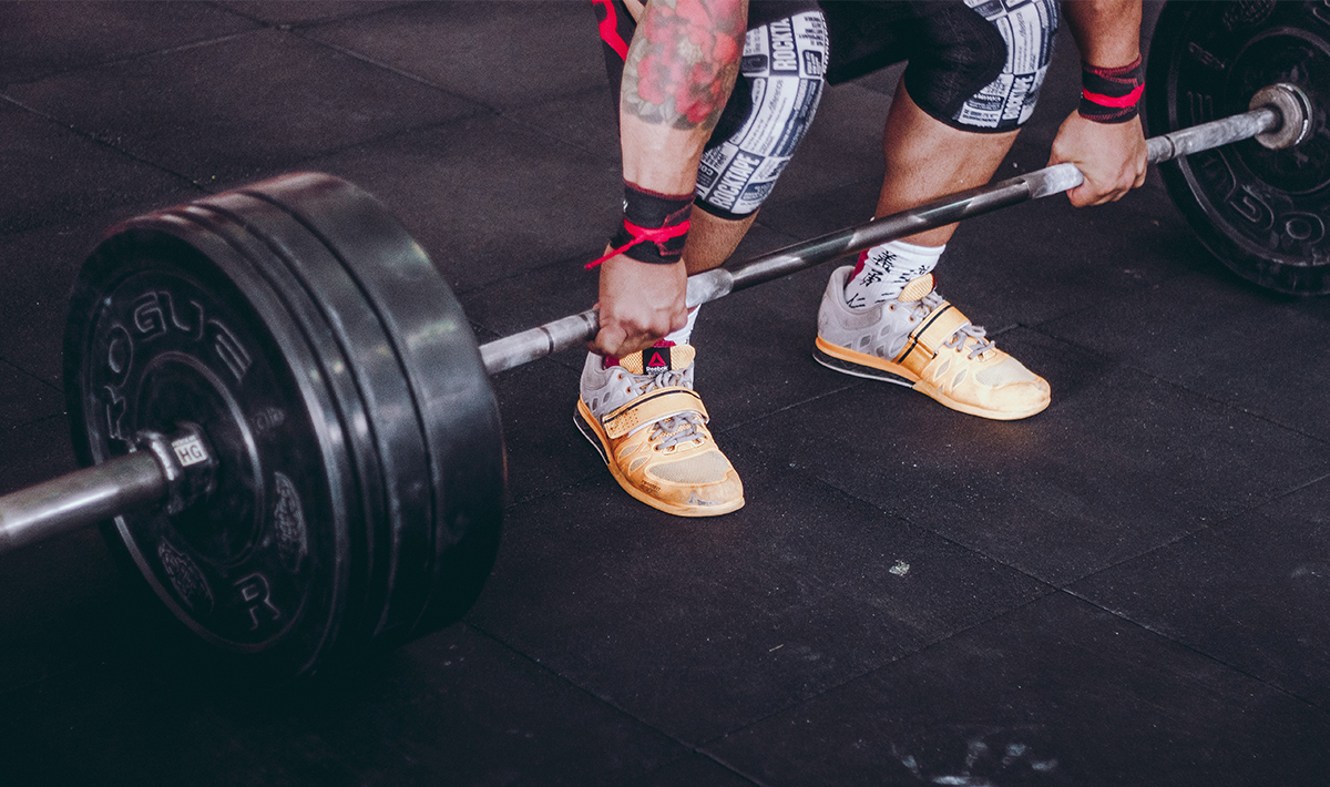 Man with tattoos lifting weights.