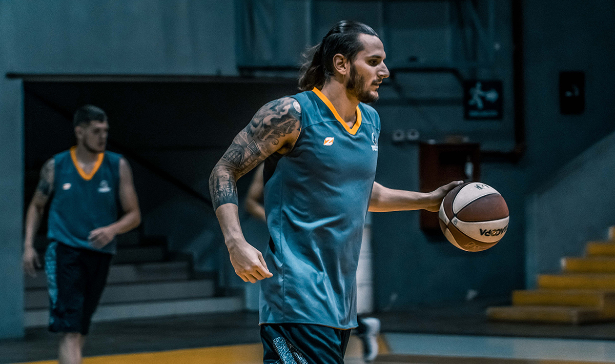 Man with tattoos playing basketball.