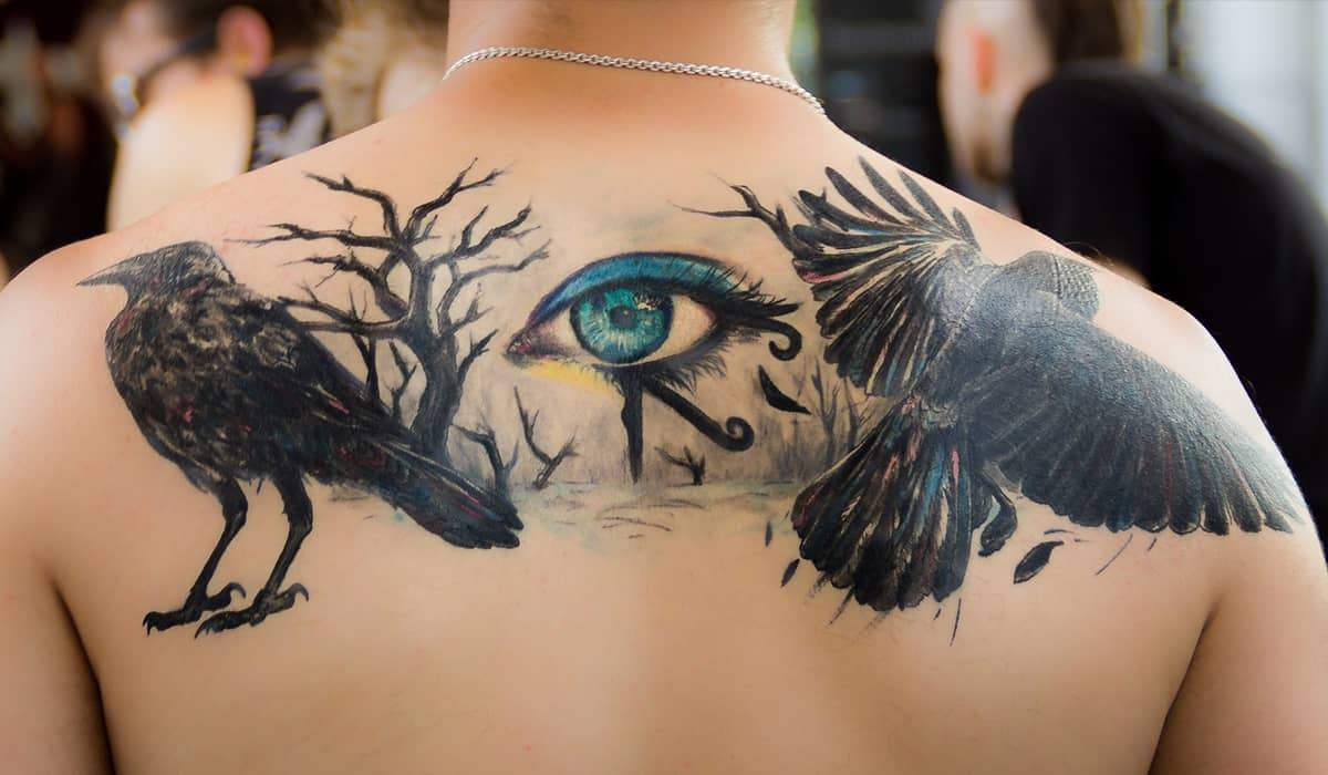Back tattoo of a raven and eye with limited colour.